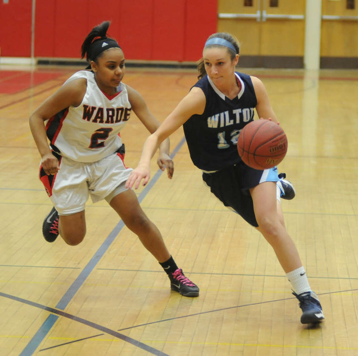 Haley English of Wilton, right, drives past a Fairfield Warde defender.