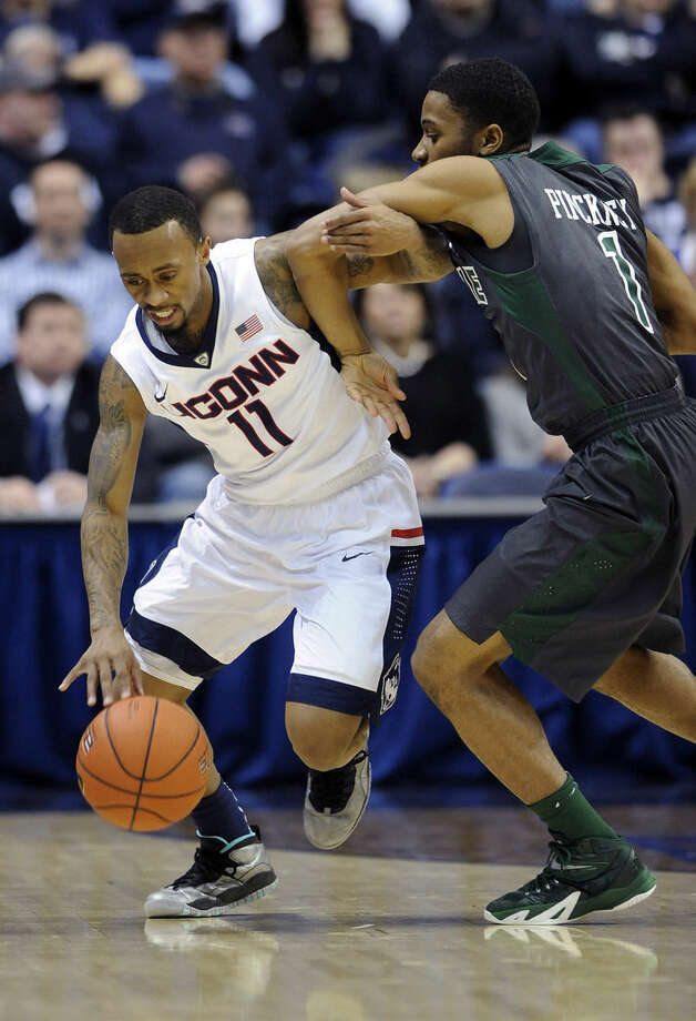 Connecticut's Ryan Boatright (11) is fouled by Tulane's Keith Pinckney (1) during the first half of an NCAA college basketball game, Sunday, Feb. 22, 2015, in Storrs, Conn. (AP Photo/Fred Beckham)