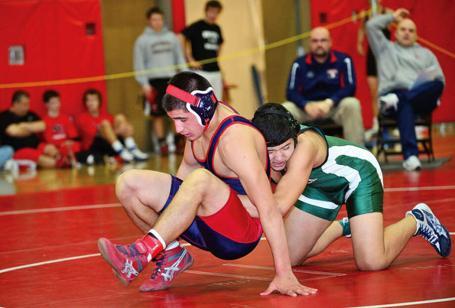 Hour photo / Erik Trautmann Brien McMahon's Ryan Retsivo wrestles Norwalk High's Franklin Cerrone at 170 in the FCIAC wrestling championship meet at New Canaan High School Saturday.