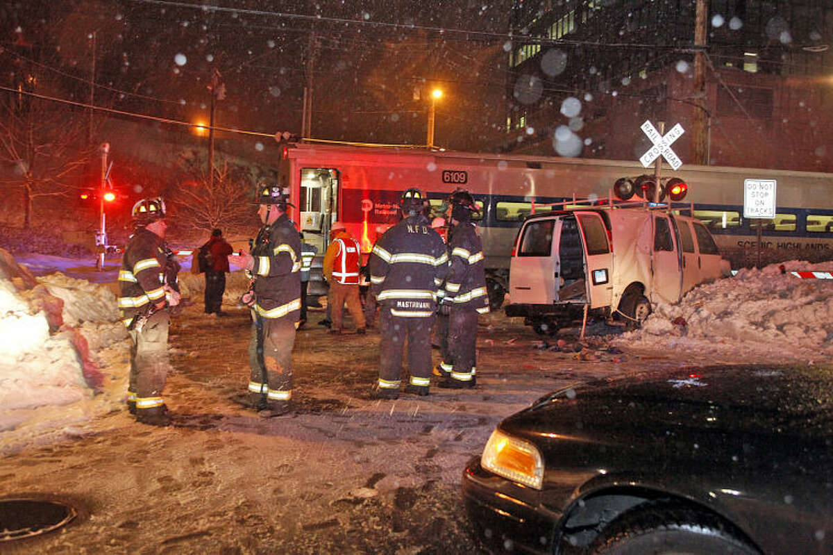 Hour Photo / Danielle Calloway Responders work on the scene of an acccident where an MTA train crashed with a van on Glover Avenue in Norwalk Saturday evening.