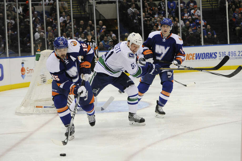 New York Islanders right wing Cal Clutterbuck (15) drives the puck away from Vancouver Canucks right wing Derek Dorsett (51) as Islanders defenseman Thomas Hickey (14) defends in the first period of an NHL hockey game at Nassau Coliseum on Sunday, Feb. 22, 2015, in Uniondale, N.Y. (AP Photo/Kathy Kmonicek)