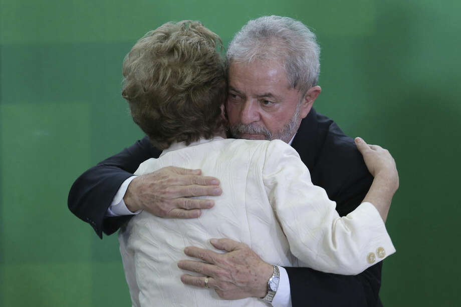 Brazil's President Dilma Rousseff and former President Luiz Inacio Lula da Silva embrace during his swearing-in ceremony as the chief of staff, at the Planalto presidential palace, in Brasilia, Brazil, Thursday, March 17, 2016. Silva was sworn in as his successor's chief of staff on Thursday and Rousseff insisted he would help put the troubled country back on track and denounced attempts to oust her. (AP Photo/Eraldo Peres)