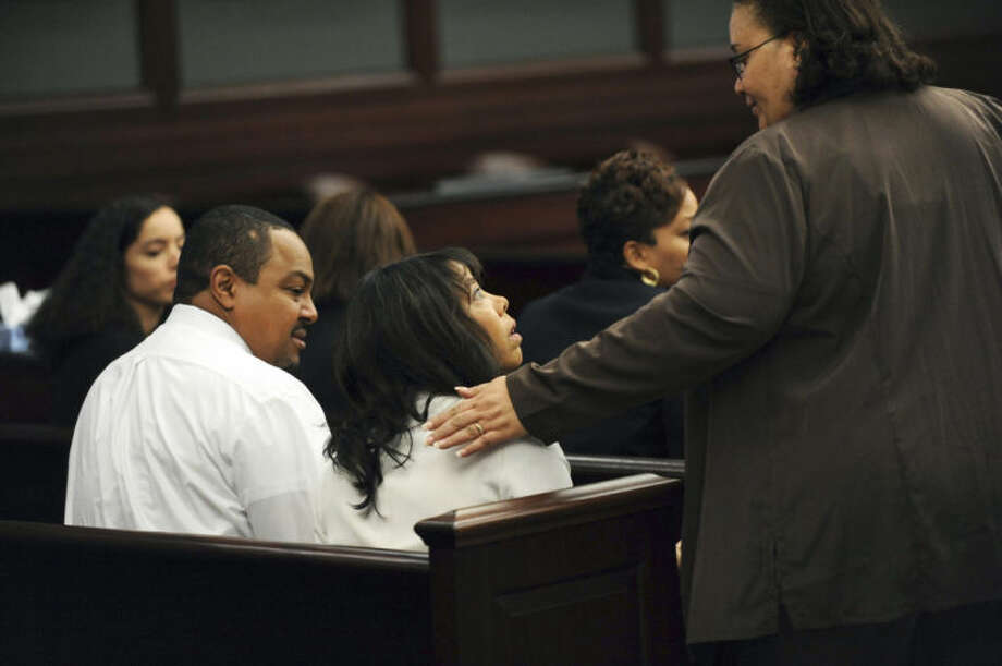 Lucia McBath, center, mother of Jordan Davis, is greeted by an unidentified woman who sat with the family in the courtroom, Saturday, Feb. 15, 2014 in Jacksonville, Fla. Her husband, Curtis McBath sits to her left. A jury begins their fourth day of deliberations Saturday in the trial of Michael Dunn, who is charged with fatally shooting 17-year-old Jordan Davis after an argument over loud music outside a Jacksonville convenient store in 2012. As of Friday, they had deliberated for 22 hours over three days. (AP Photo/The Florida Times-Union, Bob Mack, Pool)