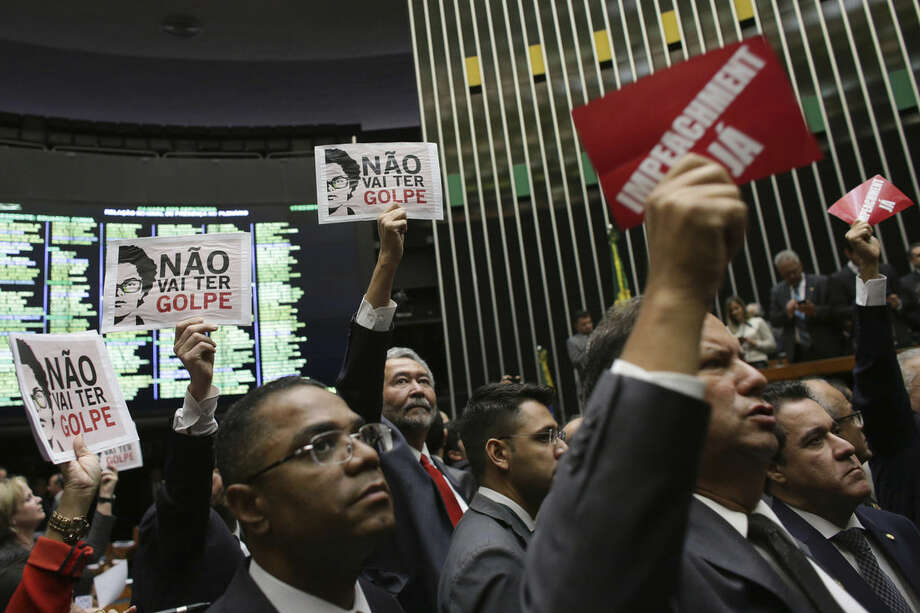 """Opposition lawmakers, right, hold up placards with a message that reads in Portuguese; """"Impeachment Now"""", while standing behind them are pro-government legislators holding sheets of paper printed with images of Brazil's President Dilma Rousseff and the message,""""There will be no coup"""", during the formation of a committee on whether to begin impeachment proceedings against Rousseff, in Brazil's lower house, in Brasilia, Thursday, March 17, 2016. (AP Photo/Eraldo Peres)"""