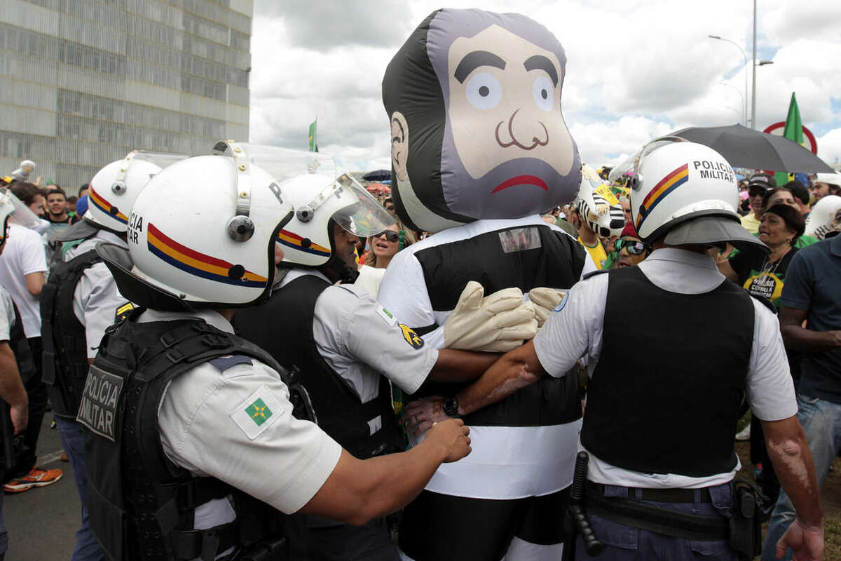 An anti-government protestor dressed in an inflatable costume in the the likeness of former President Luiz Inacio Lula da Silva in prison stripes, is pushed back by police during demonstrations in front of the Planalto presidential palace, in Brasilia, Brazil, Thursday, March 17, 2016. Silva was sworn in as his successor's chief of staff on Thursday. President Dilma Rousseff insisted he would help put the troubled country back on track while denouncing attempts to oust her. (AP Photo/Joedson Alves)