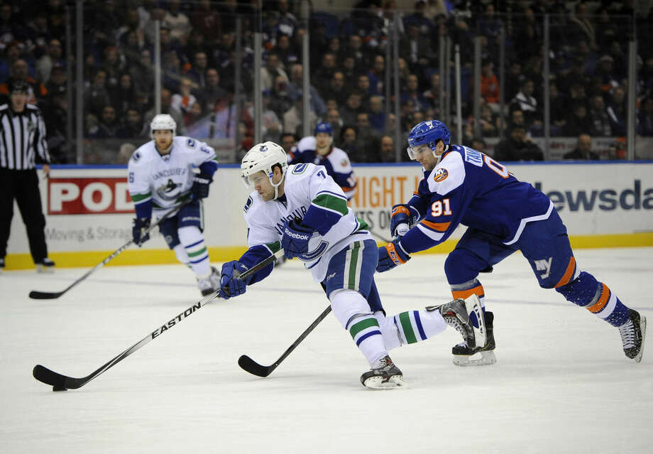 Vancouver Canucks right wing Linden Vey (7) drives the puck down ice away from New York Islanders center John Tavares (91) in the first period of an NHL hockey game at Nassau Coliseum on Sunday, Feb. 22, 2015, in Uniondale, N.Y. (AP Photo/Kathy Kmonicek)
