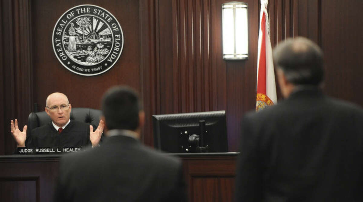 Judge Russell Healey, left rear, explains his answers to three related jury questions to defense attorney Cory Strolla, center, and defendant Michael Dunn, right, before bringing the jury into the courtroom, Saturday, Feb. 15, 2014 in Jacksonville, Fla. A jury begins their fourth day of deliberations Saturday in the trial of Dunn, who is charged with fatally shooting 17-year-old Jordan Davis after an argument over loud music outside a Jacksonville convenient store in 2012. As of Friday, they had deliberated for 22 hours over three days. (AP Photo/The Florida Times-Union, Bob Mack, Pool)