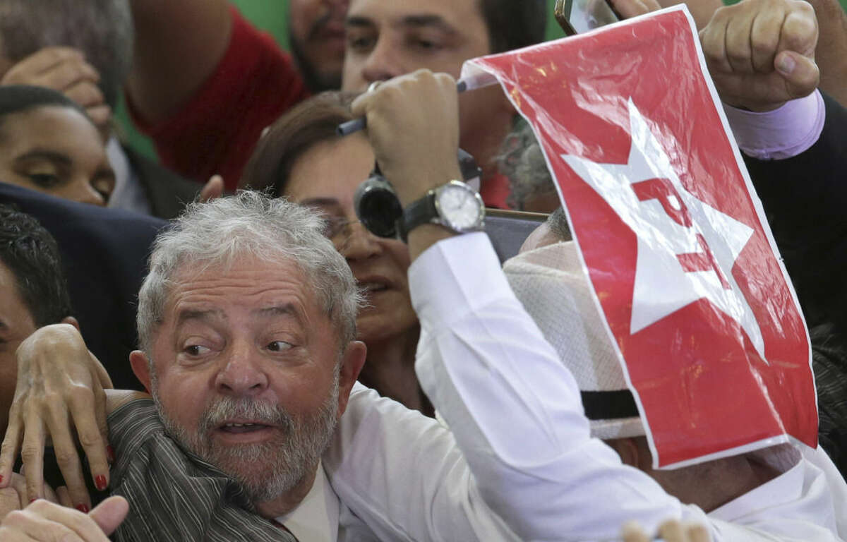Brazil's former President Luiz Inacio Lula da Silva is hugged by supporters after his swearing-in ceremony as the chief of staff to President Dilma Rousseff, at the Planalto presidential palace, in Brasilia, Brazil, Thursday, March 17, 2016. Silva was sworn in as his successor's chief of staff on Thursday. Rousseff insisted Silva would help put the troubled country back on track and denounced attempts to oust her. Supporter on the right is holding a flag that represents Brazil's governing party. (AP Photo/Eraldo Peres)