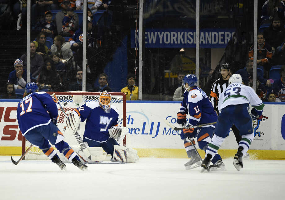 Vancouver Canucks center Bo Horvat (53) shoots the puck past New York Islanders goalie Jaroslav Halak (41) to score as Islanders left wing Matt Martin (17) and defenseman Lubomir Visnovsky (11) defend in the second period of an NHL hockey game at Nassau Coliseum on Sunday, Feb. 22, 2015, in Uniondale, N.Y. (AP Photo/Kathy Kmonicek)