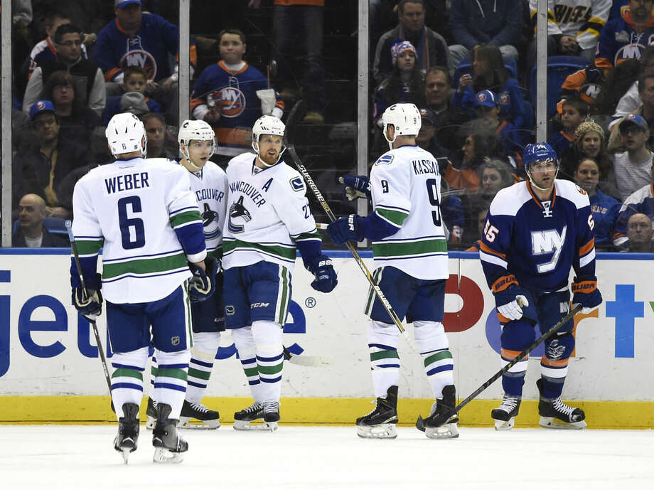Vancouver Canucks defenseman Yannick Weber (6), right wing Radim Vrbata (17), left wing Daniel Sedin (22) and right wing Zack Kassian (9) celebrate Vrbata's goal as New York Islanders defenseman Johnny Boychuk (55) skates away in the second period of an NHL hockey game at Nassau Coliseum on Sunday, Feb. 22, 2015, in Uniondale, N.Y. (AP Photo/Kathy Kmonicek)
