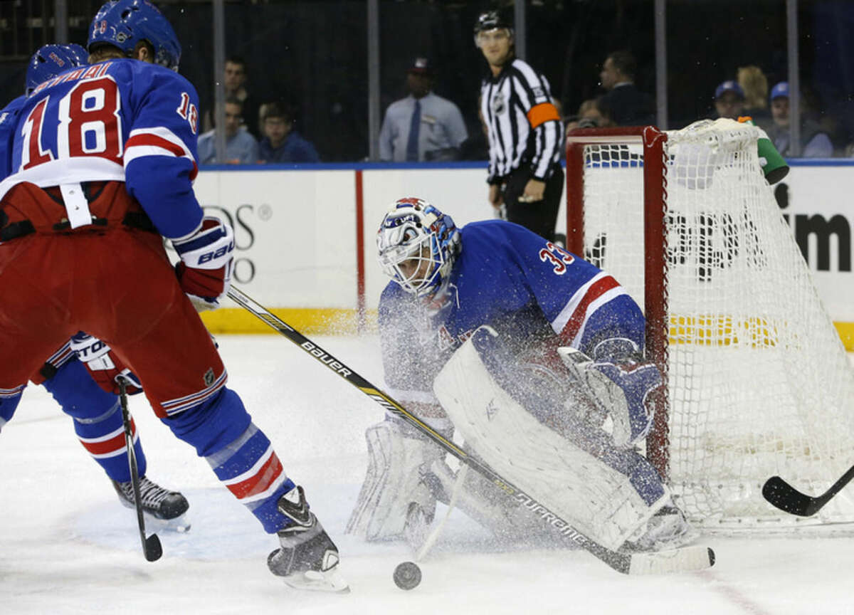 New York Rangers goalie Cam Talbot (33) makes a save in the first period of an NHL hockey game against the Columbus Blue Jackets at Madison Square Garden in New York, Sunday, Feb. 22, 2015. New York Rangers defenseman Marc Staal (18) watches, left. (AP Photo/Kathy Willens)