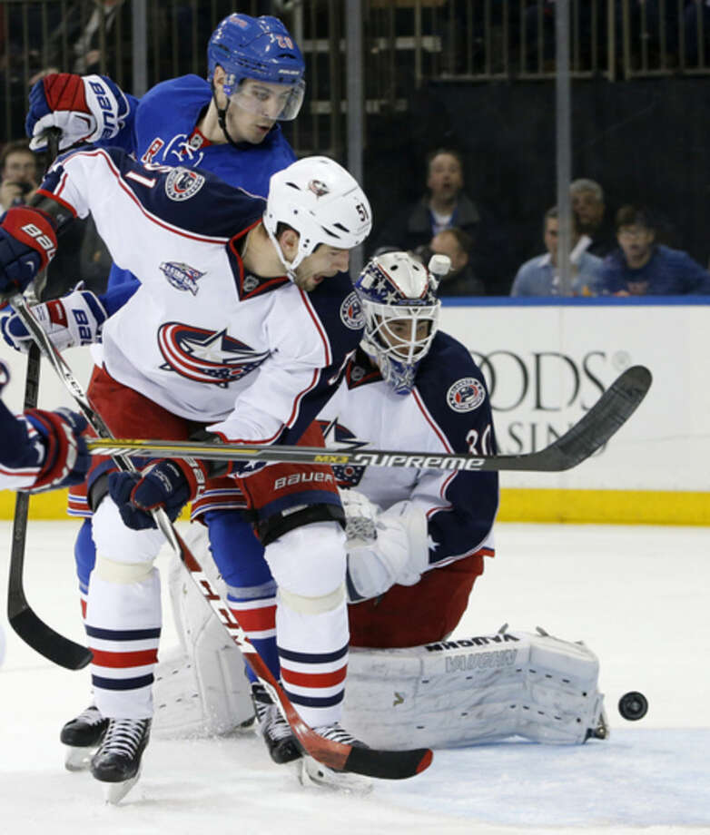 New York Rangers left wing Chris Kreider (20), Columbus Blue Jackets defenseman Fedor Tyutin (51) of Russia and Blue Jackets goalie Curtis McElhinney (30) watch as the puck skips behind McElhinney in the second period of an NHL hockey game at Madison Square Garden in New York, Sunday, Feb. 22, 2015. No goal was scored on the play. (AP Photo/Kathy Willens)