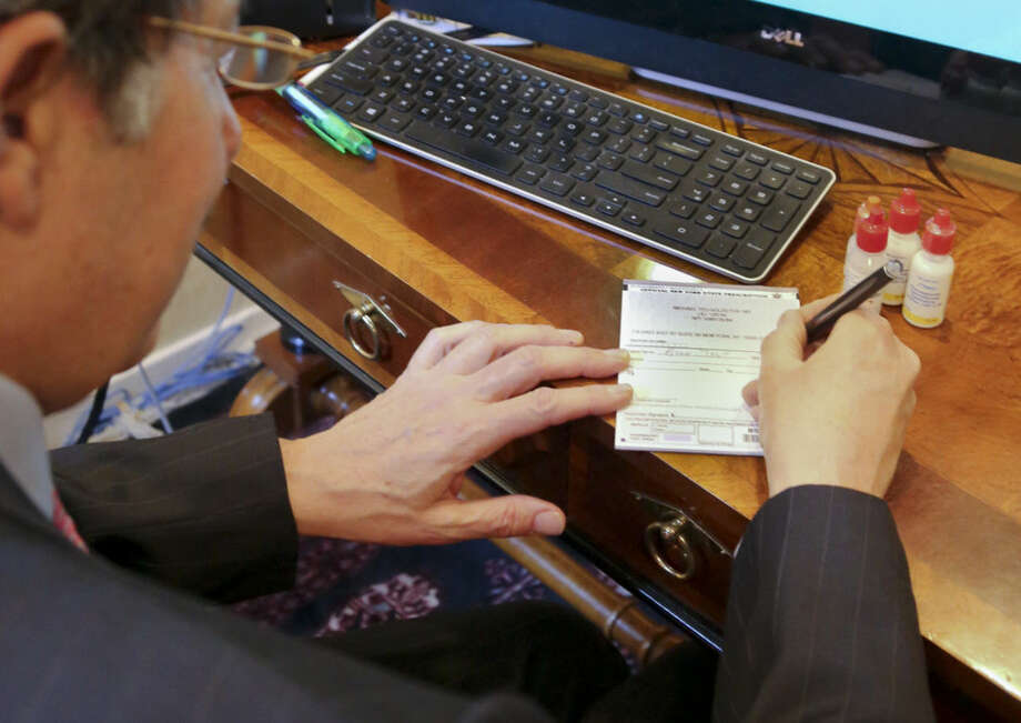 Dr. Michael T. Goldstein, New York County Medical Society President, use a standard prescription pad which is being made obsolete by a new electronic prescription law, Thursday, March 17, 2016, in New York. E-prescribing has surged nationwide in recent years. Every state now allows it, but only New York has a broad requirement that carries penalties. (AP Photo/Bebeto Matthews)