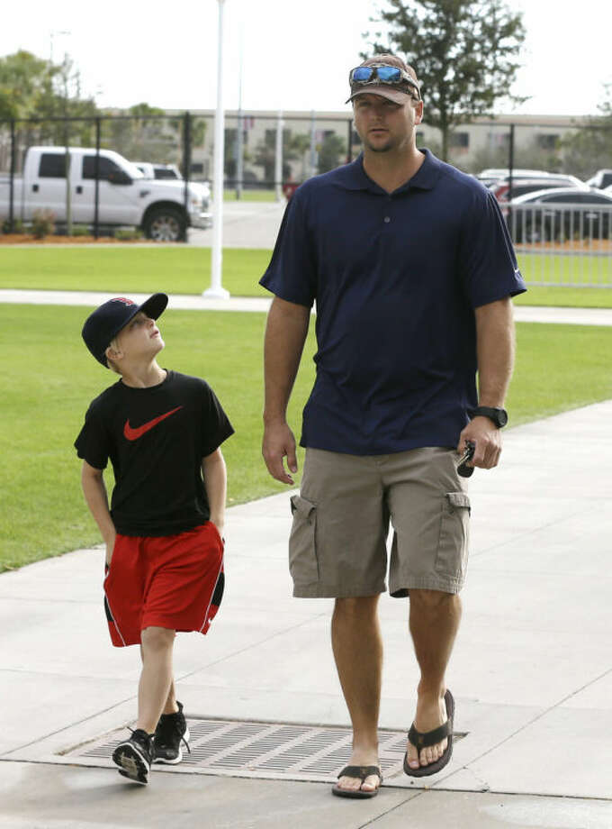 Boston Red Sox catcher A.J. Pierzynski, right, walks with his son Austin as they arrive at spring training baseball practice Saturday, Feb. 15, 2014, in Fort Myers, Fla. (AP Photo/Steven Senne)