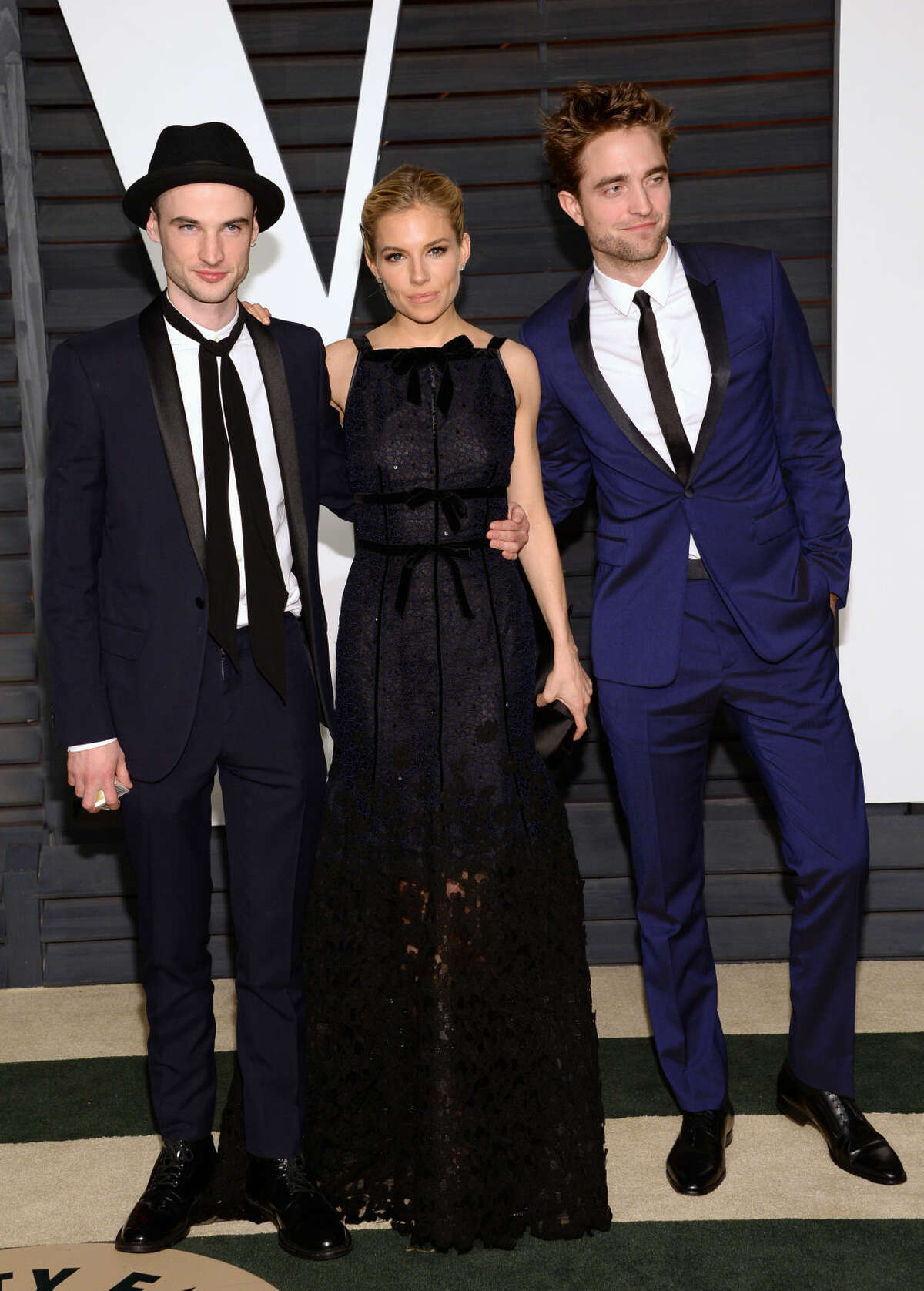 Tom Sturridge, from left, Sienna Miller, and Robert Pattinson arrive at the 2015 Vanity Fair Oscar Party on Sunday, Feb. 22, 2015, in Beverly Hills, Calif. (Photo by Evan Agostini/Invision/AP)