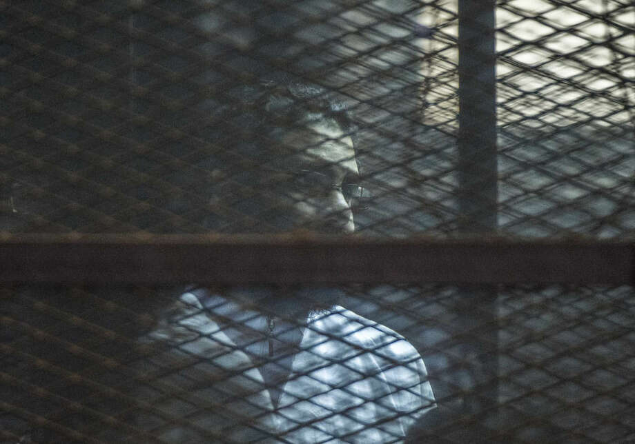 "Prominent Egyptian activist Alaa Abd el-Fattah stands in a cage during a verdict hearing for 21 people over an unauthorized street protest in 2013, in a courtroom in Cairo, Egypt, Monday, Feb. 23, 2015. The court sentenced Abd el-Fattah, an icon of the country's 2011 revolt to five years in prison Monday, showing authorities' determination to continue to stifle dissent despite promises by its president to release ""wrongly jailed youths."" Another defendant, Ahmed Abdel Rahman, was also given five years. Nineteen others were sentenced to three years. (AP Photo)"