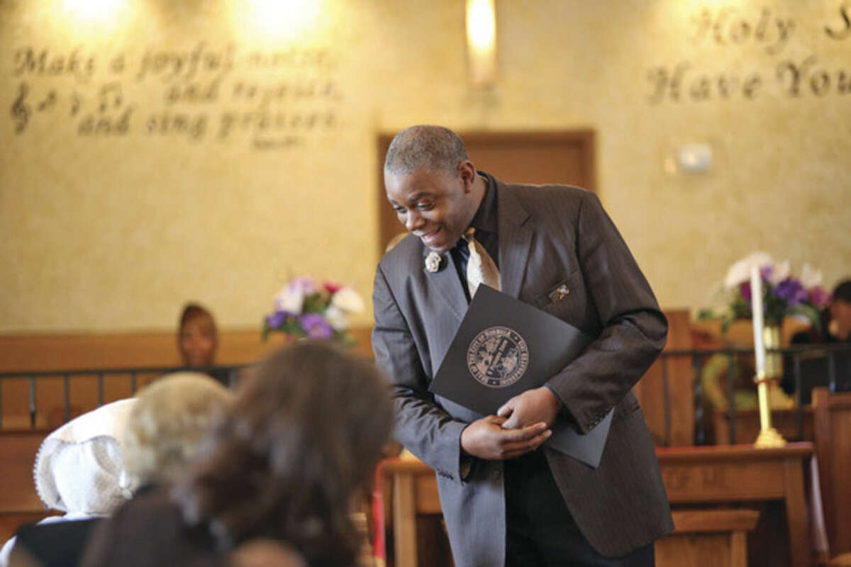 Hour photos/Danielle Calloway The Rev. Kenneth DuBose greets a church member during St. James Church's Black History event Sunday afternoon.
