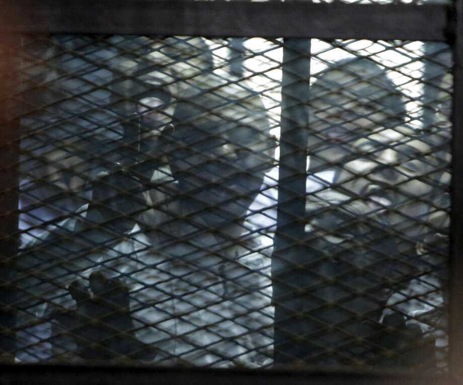 """Imprisoned Egyptian activists give the """"V"""" sign and stick out their tounges as they stand in a courtroom cage during the reading of their verdicts in Cairo, Egypt, Monday, Feb. 23, 2015. The court sentenced Alaa Abd el-Fattah, an icon of the country's 2011 revolt to five years in prison Monday, showing authorities' determination to continue to stifle dissent despite promises by its president to release """"wrongly jailed youths."""" Another defendant, Ahmed Abdel Rahman, was also given five years. The others were sentenced to three years. (AP Photo/Amr Nabil)"""