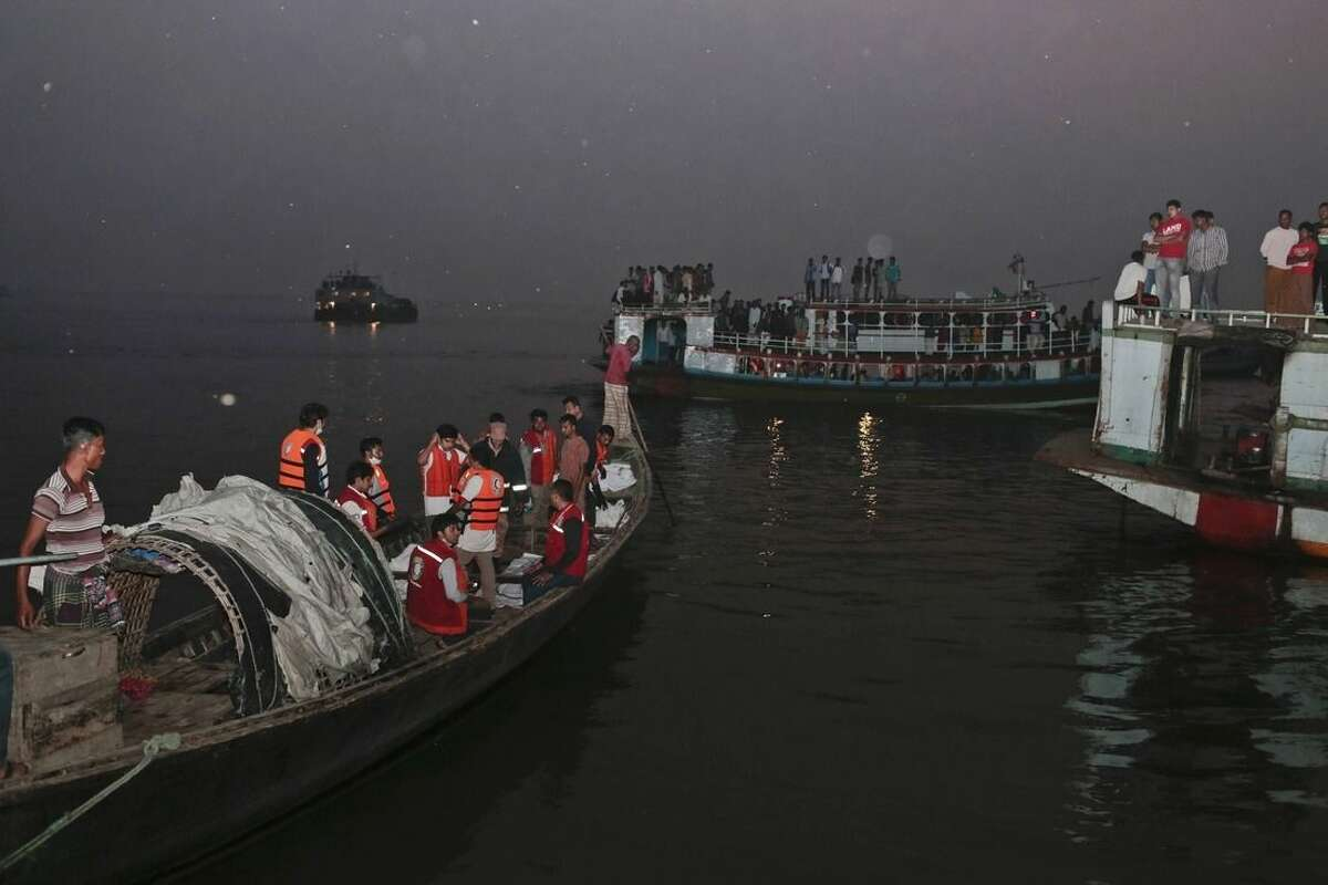 Bangladeshi rescue workers bring dead bodies of victims in a boat after a river ferry carrying about 100 passengers capsized Sunday after being hit by a cargo vessel,in Manikganj district, about 40 kilometers (25 miles) northwest of Dhaka, Bangladesh, Sunday, Feb. 22, 2015.(AP Photo/ A.M. Ahad)