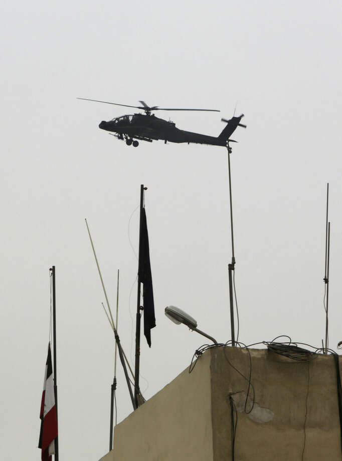 """An Egyptian military helicopter flies over Tora prison in Cairo, Egypt, Monday, Feb. 23, 2015. An Egyptian court sentenced Alaa Abd el-Fattah, an icon of the country's 2011 revolt to five years in prison Monday, showing authorities' determination to continue to stifle dissent despite promises by its president to release """"wrongly jailed youths."""" Another defendant, Ahmed Abdel Rahman, was also given five years. The others were sentenced to three years. (AP Photo/Amr Nabil)"""
