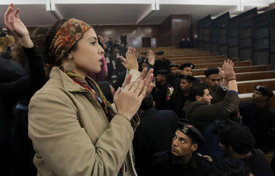 "Supporters of 21 activists on trial stand on wooden benches chanting, ""Down with military rule,"" after they were sentenced to prison terms over an unauthorized street protest in 2013, in a Cairo court, Egypt, Monday, Feb. 23, 2015. The court sentenced Alaa Abd el-Fattah, an icon of the country's 2011 revolt to five years in prison Monday, showing authorities' determination to continue to stifle dissent despite promises by its president to release ""wrongly jailed youths."" Another defendant, Ahmed Abdel Rahman, was also given five years. The others were sentenced to three years. (AP Photo/Amr Nabil)"