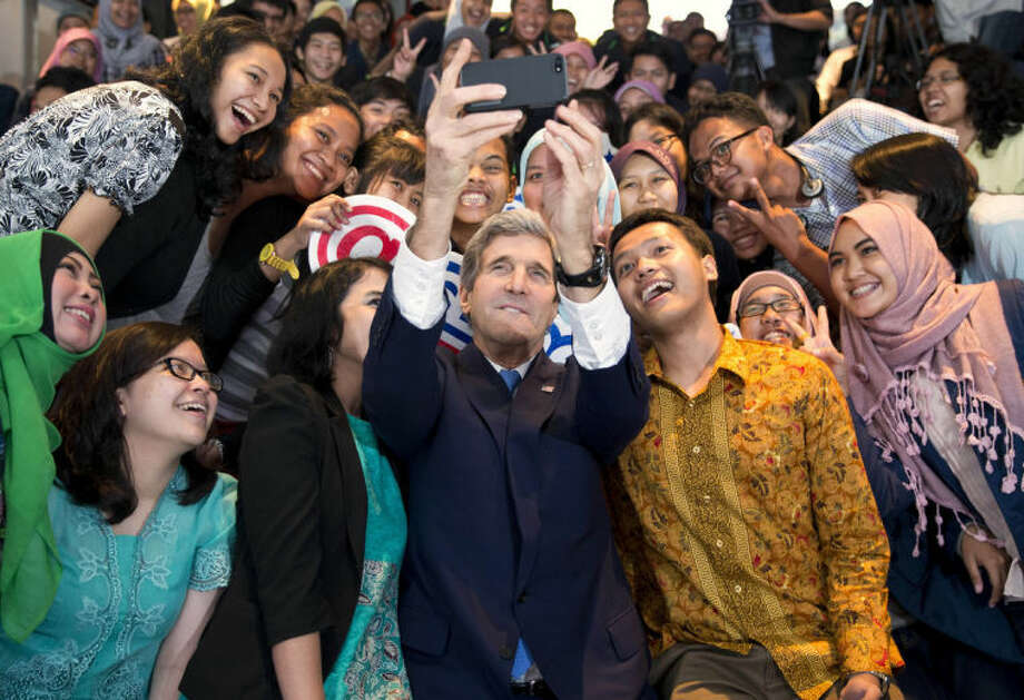 "Secretary of State John Kerry takes a selfie with a group of students before delivering a speech on climate change on Sunday, Feb. 16, 2014, in Jakarta. Kerry called for a ""global solution"" for climate change in the first of several speeches he will deliver this year on the topic. (AP Photo/ Evan Vucci, Pool)"