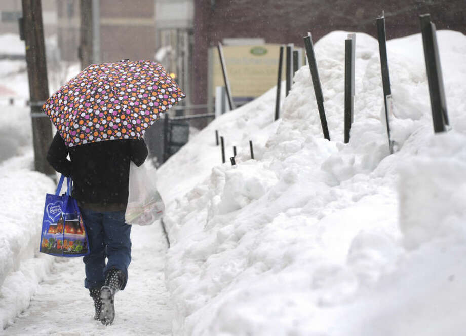 AP Photo/York Daily Record, Jason PlotkinPam Yeaple walks home along East Philadelphia Street after grocery shopping in York, Pa. on Saturday, Feb. 15, 2014. An inch of new snow had fallen by mid-day in much of eastern Pennsylvania on Saturday.