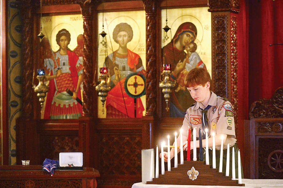 Hour photo / Erik Trautmann A boy scout performs the Lighting of Scout Law and Oath Candles as Sean Walters is honored during the Boy Scout Eagle Court of Honor ceremony at St. George Greek Orthodox Church where Walters was awarded the Eagle Scout Badge with the help of his family and dignitaries Saturday afternoon.
