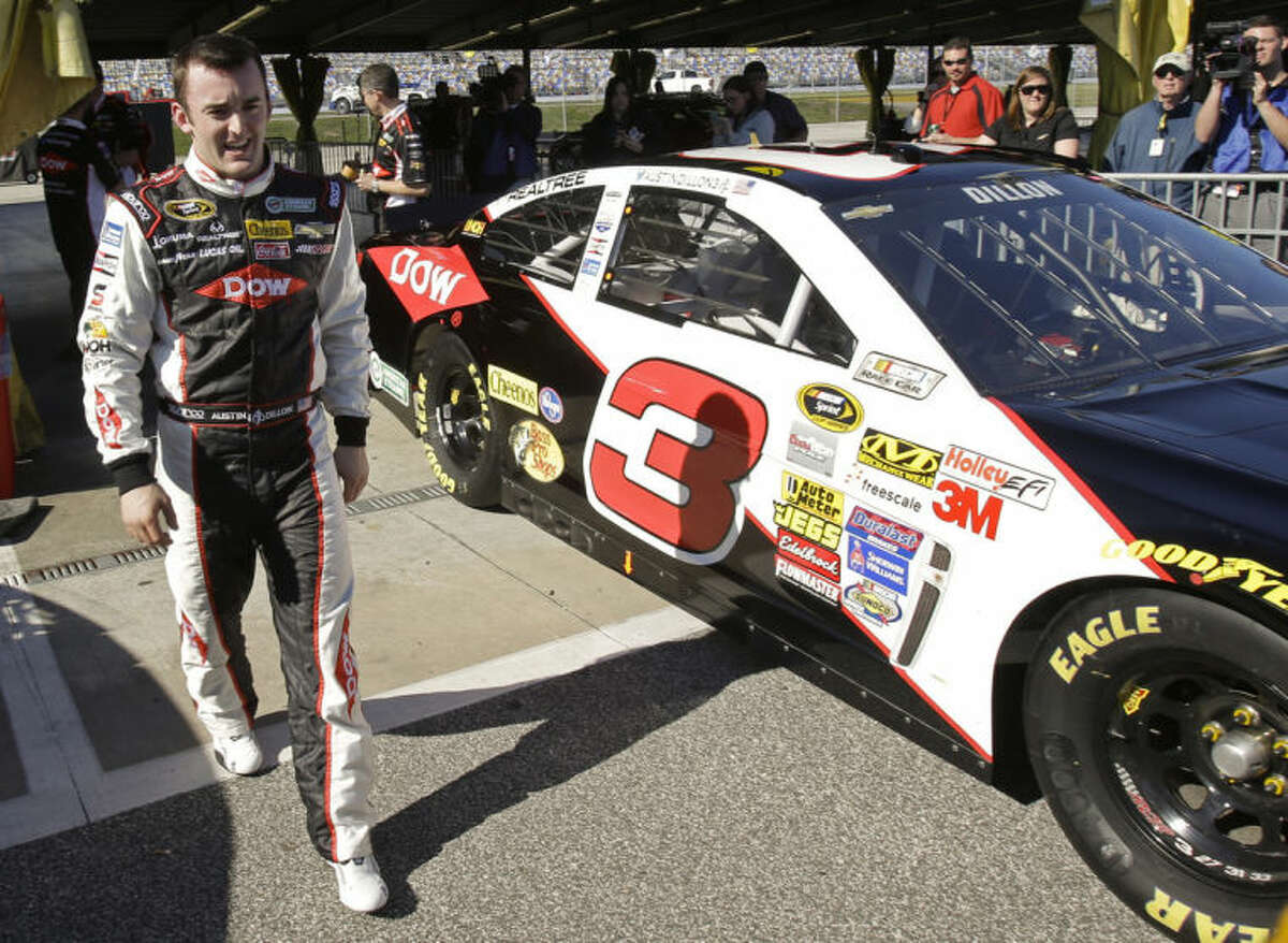 Austin Dillion walks by his car in the garage area after he won the pole position during qualifying for the Daytona 500 NASCAR Sprint Cup Series auto race at Daytona International Speedway in Daytona Beach, Fla., Sunday, Feb. 16, 2014. (AP Photo/John Raoux)