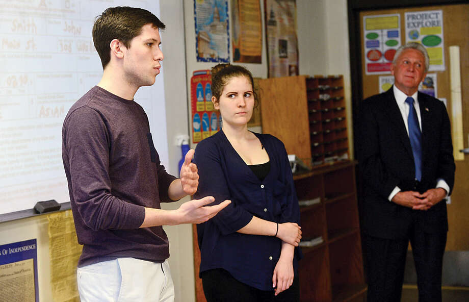 Hour photo / Erik Trautmann Students, Connor D'Amico and Kasey Macedo, debate opposing political ideology as Norwalk Mayor Harry Rilling teaches a civics class at the mayor's alma mater, Norwalk High School, Wednesday morning.