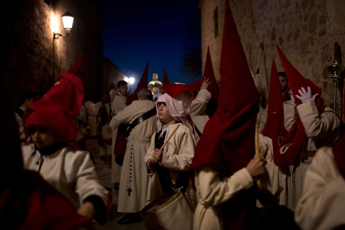 Penitents wait outside the church before taking part in a procession, during the Holy Week in Zamora, Spain, Wednesday, March 23, 2016. Hundreds of processions take place throughout Spain during the Easter Holy Week. (AP Photo/Emilio Morenatti)