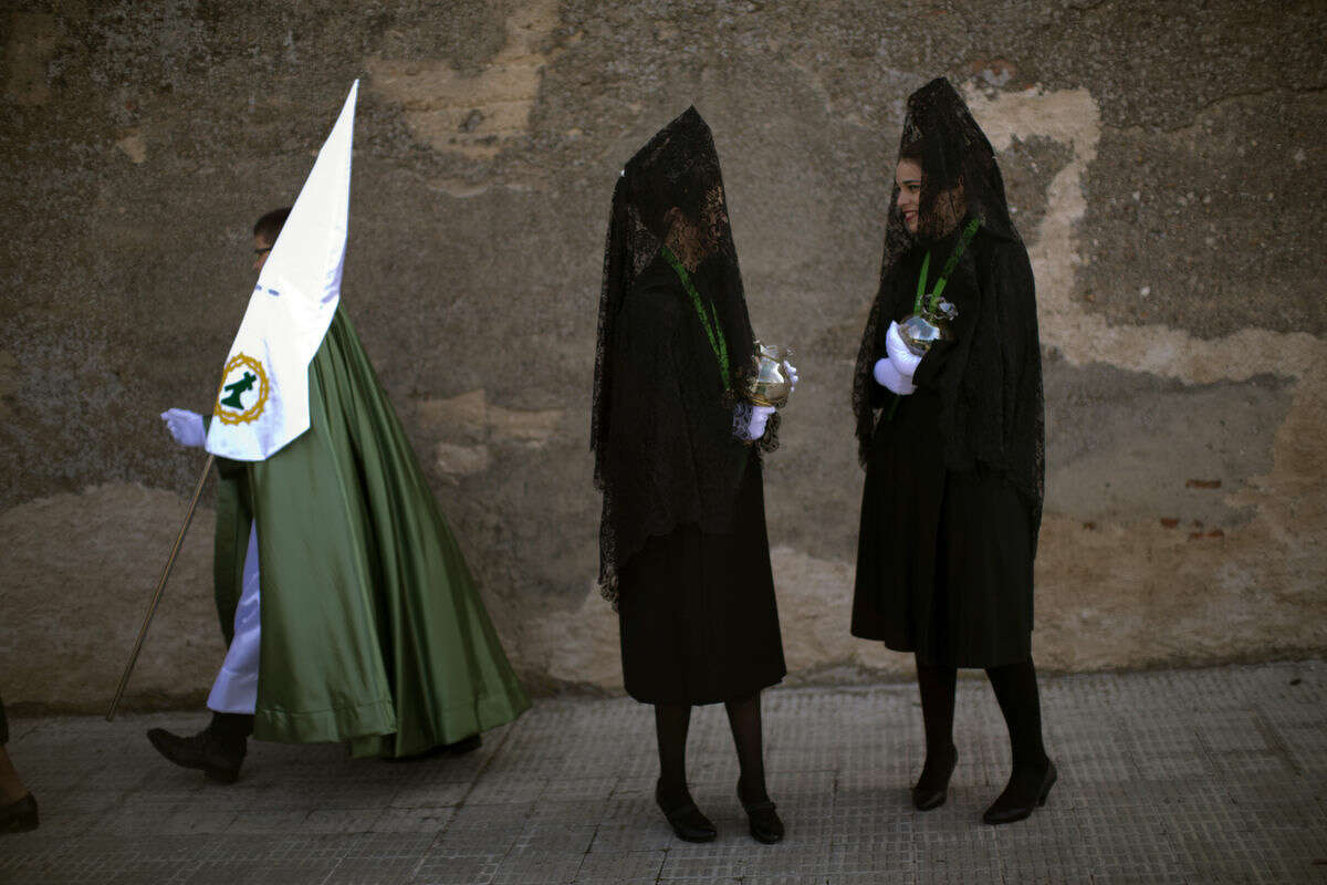 A penitent walks past women wearing the traditional mantilla, as they wait to take part in the