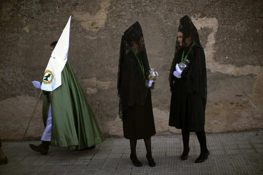 "A penitent walks past women wearing the traditional mantilla, as they wait to take part in the ""Procesion Virgen de la Esperanza"" brotherhood, during the Holy Week in Zamora, Spain, Thursday, March 24, 2016. Hundreds of processions take place throughout Spain during the Easter Holy Week. (AP Photo/Emilio Morenatti)"