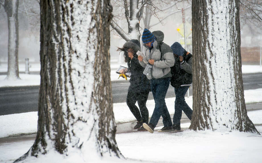 Colorado College students battle blizzard-like conditions as they cross campus Wednesday, March 23, 2016, in Colorado Springs, Colo. Heavy snow and strong winds have shut down some highways and schools in Colorado and canceled flights at Denver's airport. (Christian Murdock/The Gazette via AP)