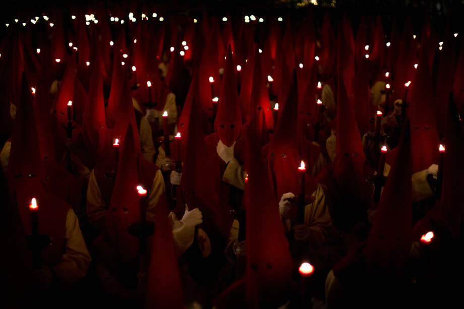 """Penitents hold their candles as they take part in the """"Procesion del Silencio"""" brotherhood, during the Holy Week in Zamora, Spain, Wednesday, March 23, 2016. Hundreds of processions take place throughout Spain during the Easter Holy Week. (AP Photo/Emilio Morenatti)"""
