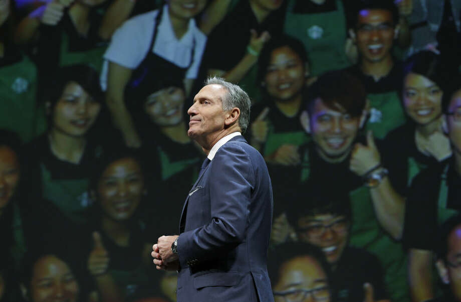 Starbucks CEO Howard Schultz walks in front of a photo of Starbucks baristas, Wednesday, March 23, 2016, at the coffee company's annual shareholders meeting in Seattle. (AP Photo/Ted S. Warren)