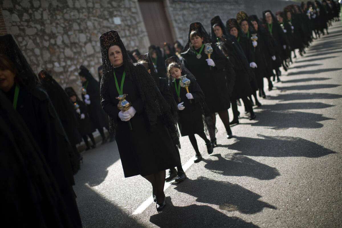 Women wearing the traditional mantilla take part in the
