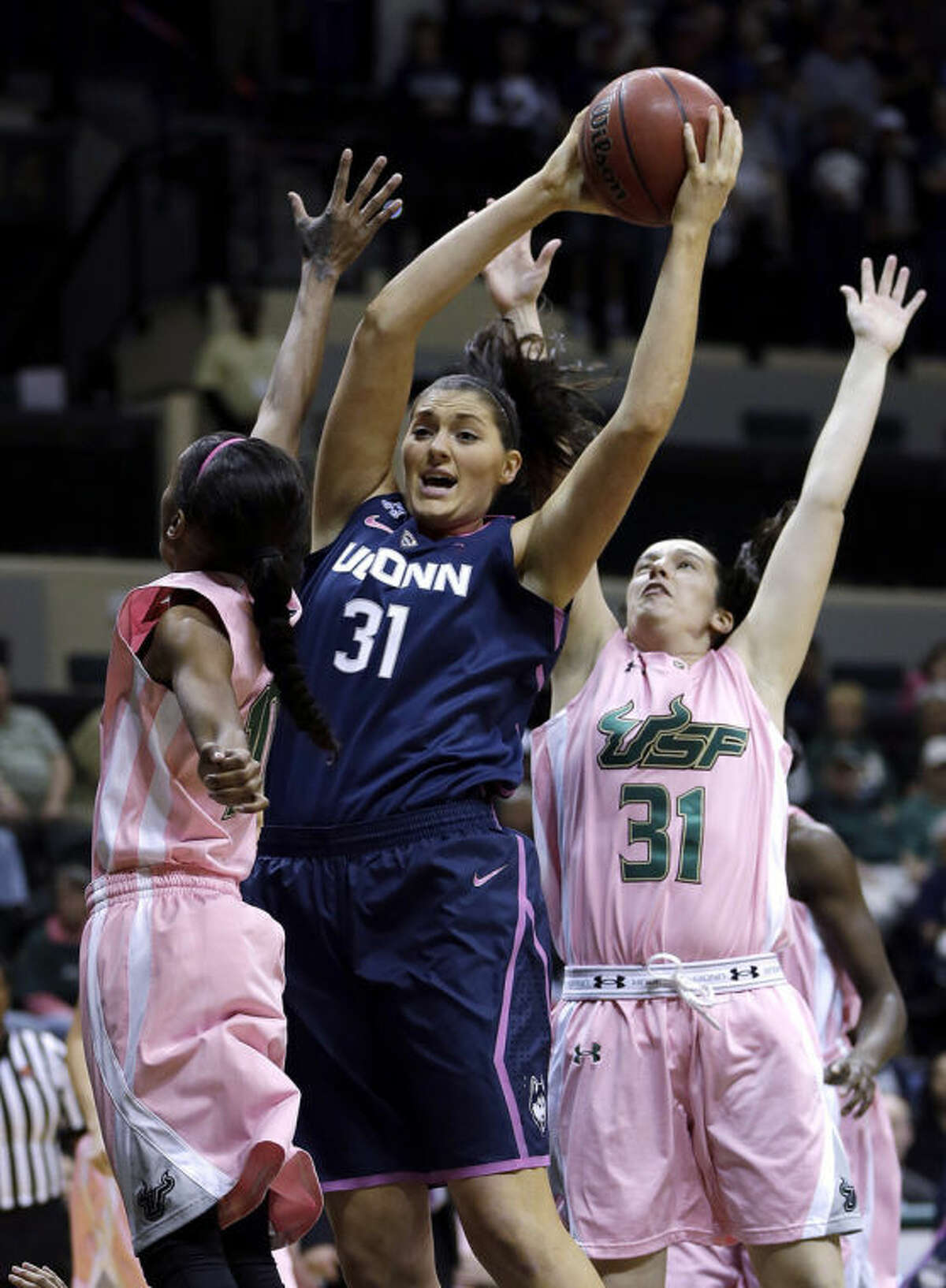 Connecticut center Stefanie Dolson (31, center) grabs a rebound away from South Florida guard Courtney Williams (10) and guard Laura Marcos Canedo (31) during the first half of an NCAA women's college basketball game, Sunday, Feb. 16, 2014, in Tampa, Fla. (AP Photo/Chris O'Meara)