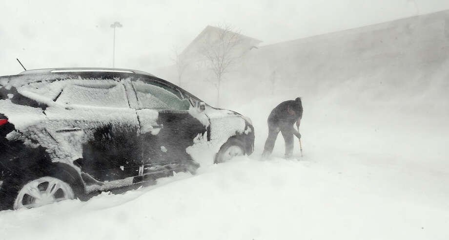 Lisa Rose tries dig her car out of a parking lot in Monument, Colo., Wednesday, March 23, 2016. A powerful spring blizzard stranded travelers at Denver's airport and shut down hundreds of miles of highway in Colorado, Wyoming and Nebraska as it spread into the Midwest on Wednesday. (Jerilee Bennett/The Gazette via AP) MAGS OUT; MANDATORY CREDIT