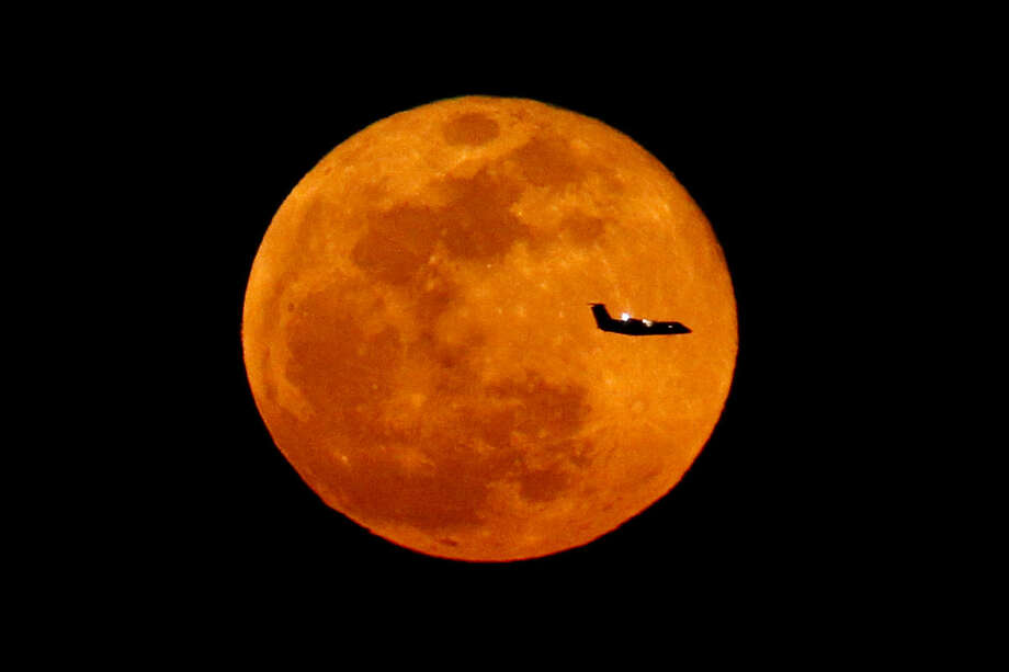A plane descending into Newark Liberty International Airport crosses over the full moon rising seen from Eagle Rock Reservation, Wednesday, March 23, 2016, in West Orange, N.J. (AP Photo/Julio Cortez)