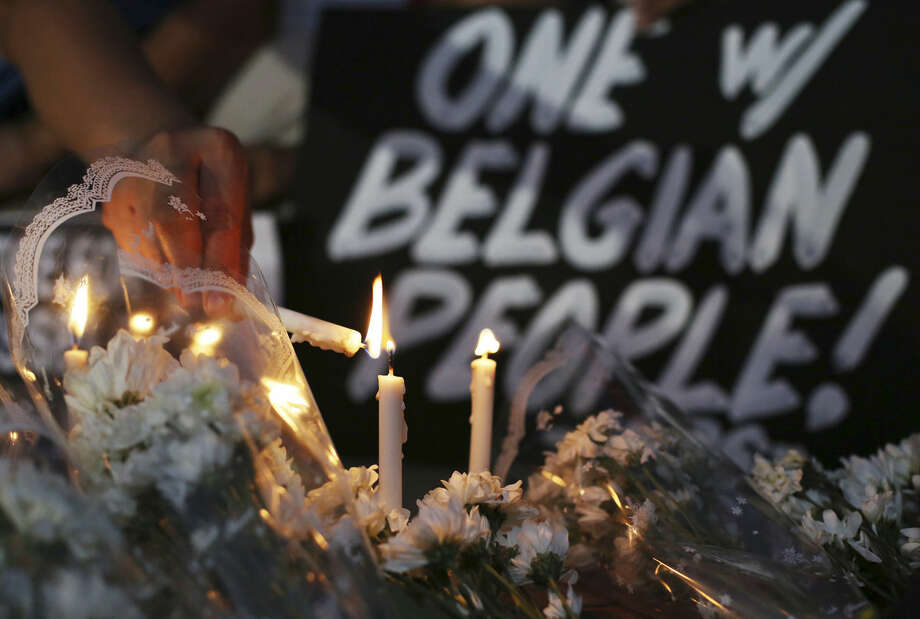 A Filipino activist lights candles among flowers offered for victims of Brussels attacks beside a condolence sign in suburban Quezon city, north of Manila, Philippines to condemn the latest attacks Wednesday, March 23, 2016. Philippine President Benigno Aquino III has ordered an extra tightening of security in all airports, seaports and public transport terminals across the country following explosions in Brussels that killed many people. (AP Photo/Aaron Favila)