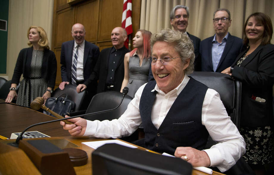 "Roger Daltrey, lead singer of the English rock band ""The Who"" and co-founder of Teen Cancer America, jokingly poses with the gavel seated on the chairman's chair in a hearing room on Capitol Hill in Washington, Wednesday, March 23, 2016, at the conclusion of a ""conversation on child cures"" hosted by the House Energy and Commerce Committee. (AP Photo/Manuel Balce Ceneta)"