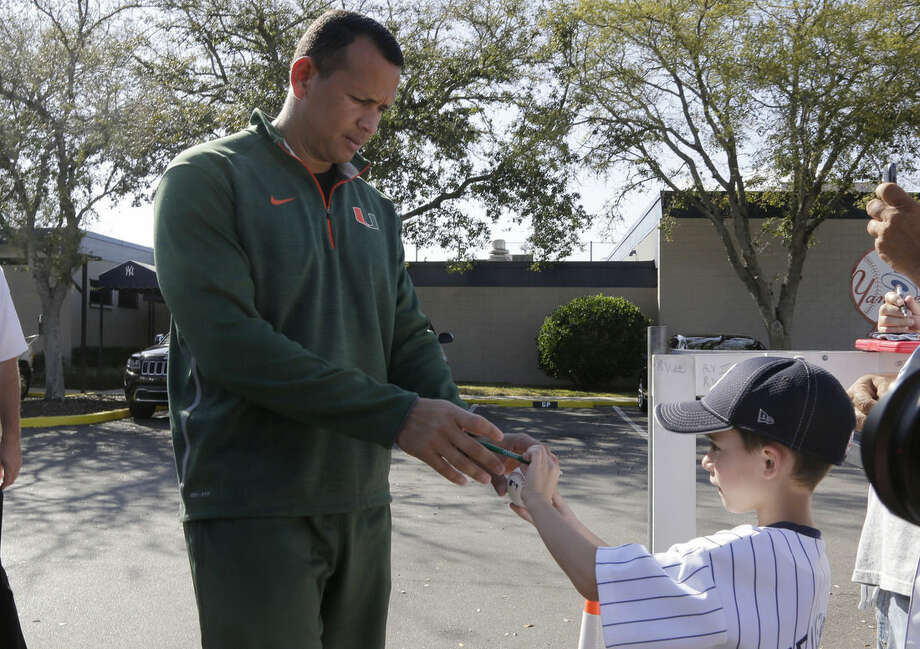 New York Yankees' Alex Rodriguez, left, signs autographs for fans following a workout for spring training baseball, at the Yankees minor league facility, Monday, Feb. 23, 2015, in Tampa, Fla. The official full squad workouts begin Feb. 26. (AP Photo/Lynne Sladky)