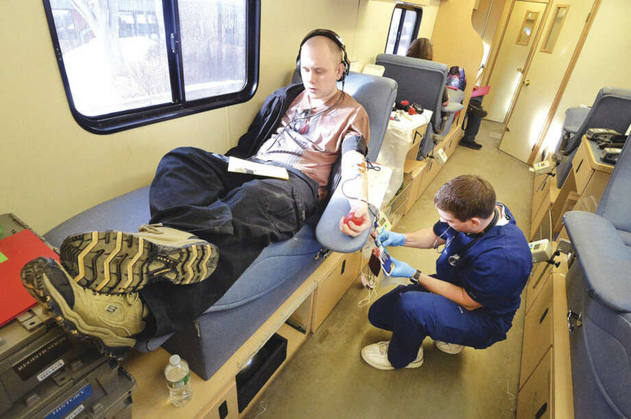 Hour photo/Alex von KleydorffNorwalk Community College student Tyler Swan relaxes as phlebotomist Chris Banziruk draws blood during an American Red Cross blood drive at NCC on Monday.