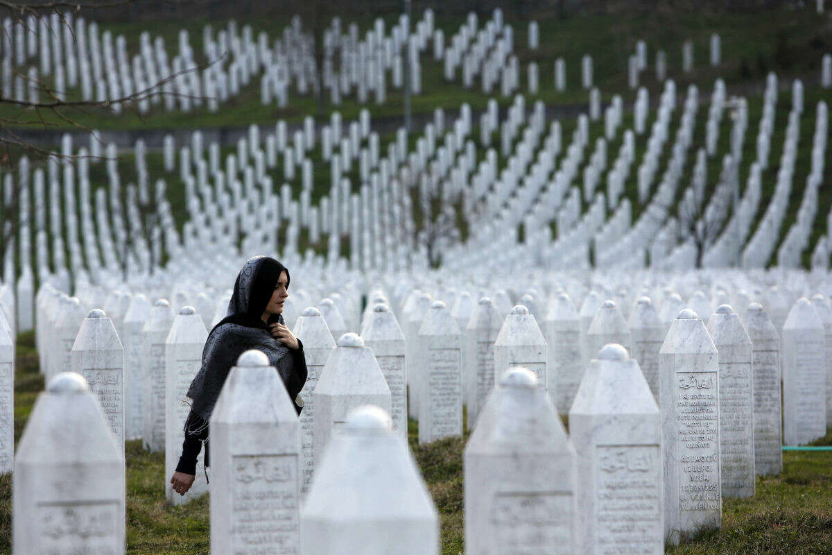 In this photo taken on Sunday, March 20, 2016, a Bosnian woman walks among gravestones at Memorial Centre Potocari near Srebrenica, Bosnia and Herzegovina. Former Bosnian Serb leader Radovan Karadzic will hear his verdict on Thursday, March 24, 2016 and prosecutors of the U.N. war crimes tribunal have called for life in prison for 11 counts of war crimes, including genocide he is accused of having masterminded during Bosnia's 1992-95 war. (AP Photo/Amel Emric)