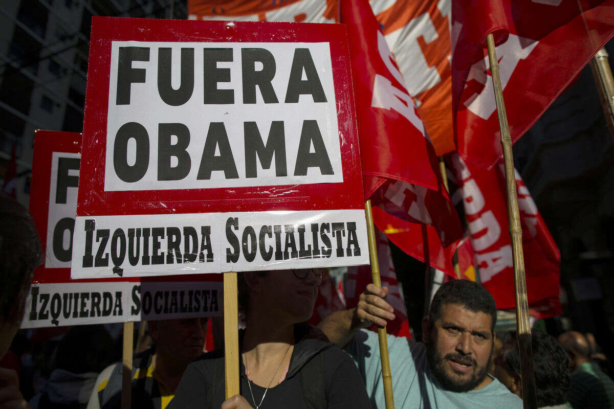 Demonstrators from the Socialist Left political party carry signs that read in Spanish: