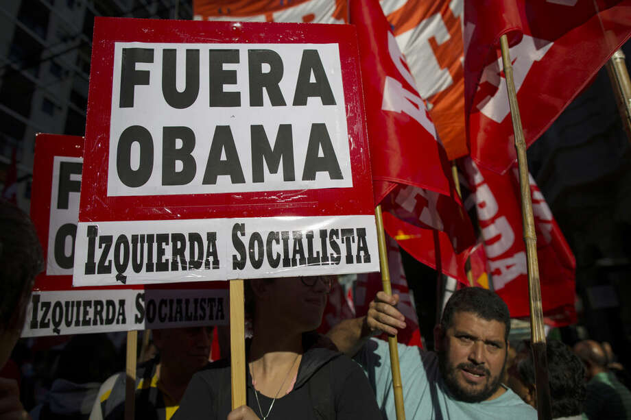 """Demonstrators from the Socialist Left political party carry signs that read in Spanish: """"Get out Obama!"""" to protest the visit of President Barack Obama, near the U.S. Embassy in Buenos Aires, Argentina, Wednesday, March 23, 2016. Human rights activists argue that during the Cold War, the U.S. backed military dictatorships, including Argentina's regime, and thus the presence of Obama on the 40th anniversary of the military coup that ushered in one of the most repressive military dictatorships in Latin American history, is disrespectful to families of the thousands who died or where disappeared. Last week, the Obama administration announced plans to declassify CIA, FBI and other secret documents related to the dictatorship. (AP Photo/Ivan Fernandez)"""