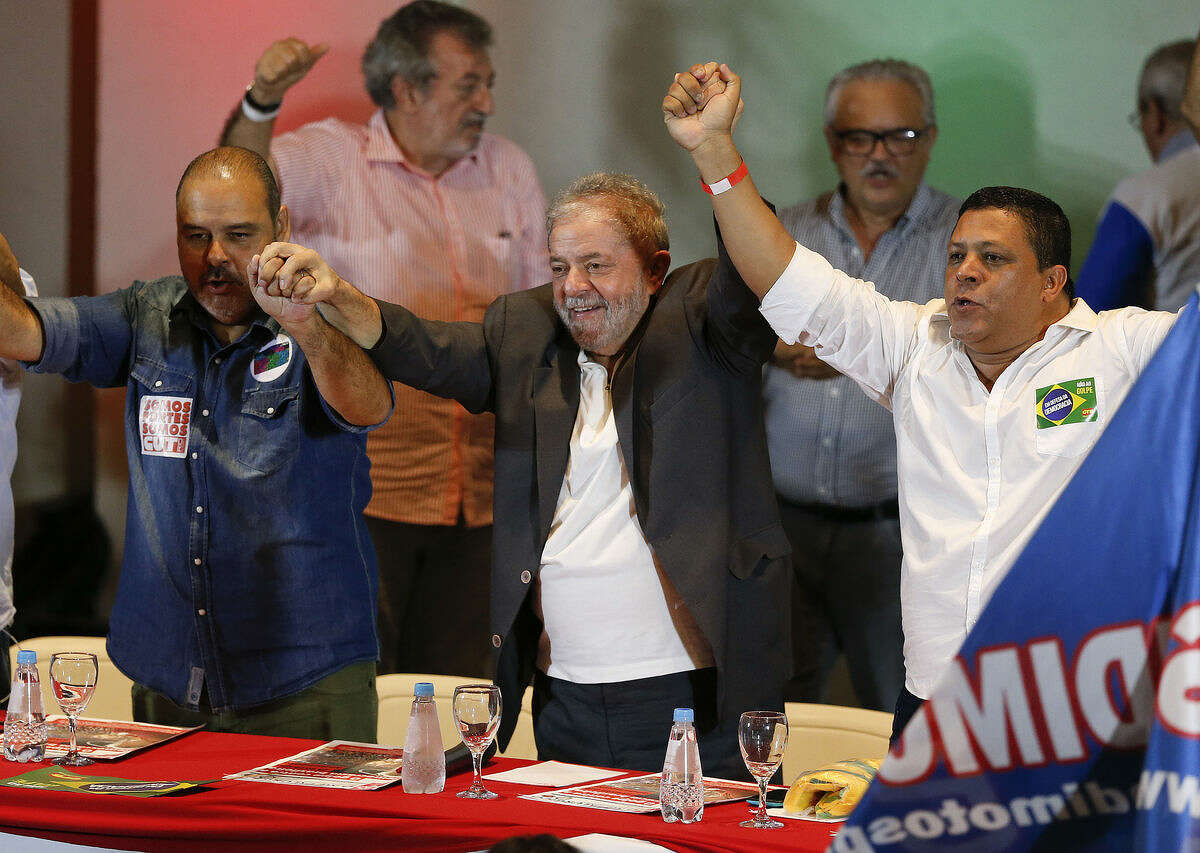 Union leaders raise the arms of Brazil's former President Luiz Inacio Lula da Silva, center, during a meeting in Sao Paulo, Brazil, Wednesday, March 23, 2016. A Brazilian Supreme Court justice said a lower court judge erred in releasing tapped phone calls of the former President and at least temporarily removed him from any investigation of the embattled ex-leader. Lula da Silva has been tied to a sprawling corruption investigation connected to the Brazilian oil giant Petrobras. (AP Photo/Andre Penner)
