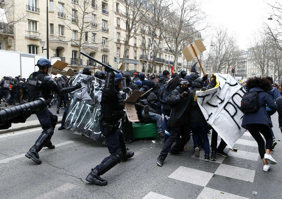 Youths clash with riot police officers during a high school students demonstration against a labor reform, in Paris, Thursday, March 24, 2016. France's Socialist government is due to formally present a contested labor reform that aims to amend the 35-hour workweek and relax other labor rules. (AP Photo/Francois Mori)