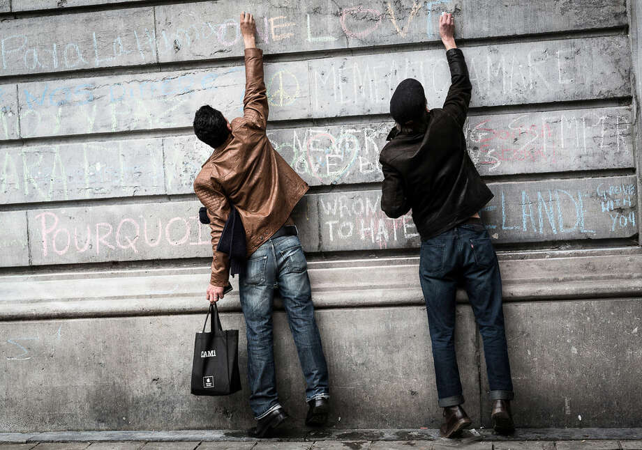 Two men write on a wall at a memorial for victims of attacks in Brussels on Wednesday, March 23, 2016. Belgian authorities were searching Wednesday for a top suspect in the country's deadliest attacks in decades, as the European Union's capital awoke under guard and with limited public transport after scores were killed and injured in bombings on the Brussels airport and a subway station. (AP Photo/Valentin Bianchi)